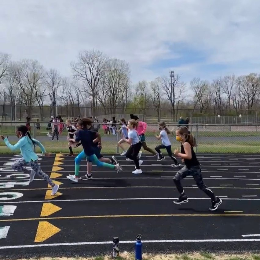 AthLead Indy youth runners sprinting across the finish line on a track for track and field with an All Kids Play youth sports financial assistance grant in Indianapolis, Indiana