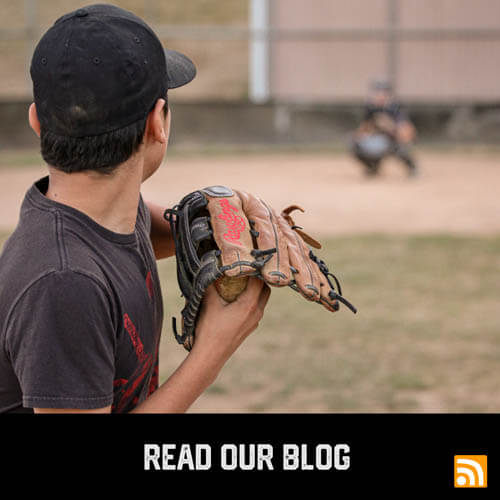 Latinx youth sports baseball player winding up to pitch to the catcher during a baseball game