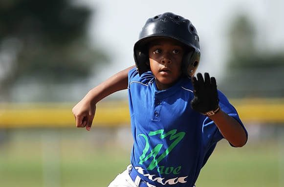 African American youth sports baseball player with batting helmet running the bases on a baseball field during a game