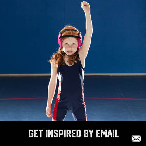Youth sports girl wrestler standing with fist up in victory after a wrestling match in a gym