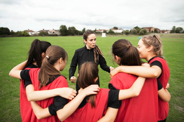 Female coach with youth sports girls soccer team in a huddle coaching and teaching during a game on a soccer field