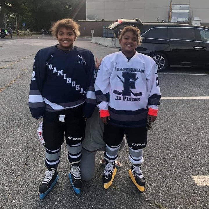 Two twin girl youth hockey players in hockey uniforms and gear