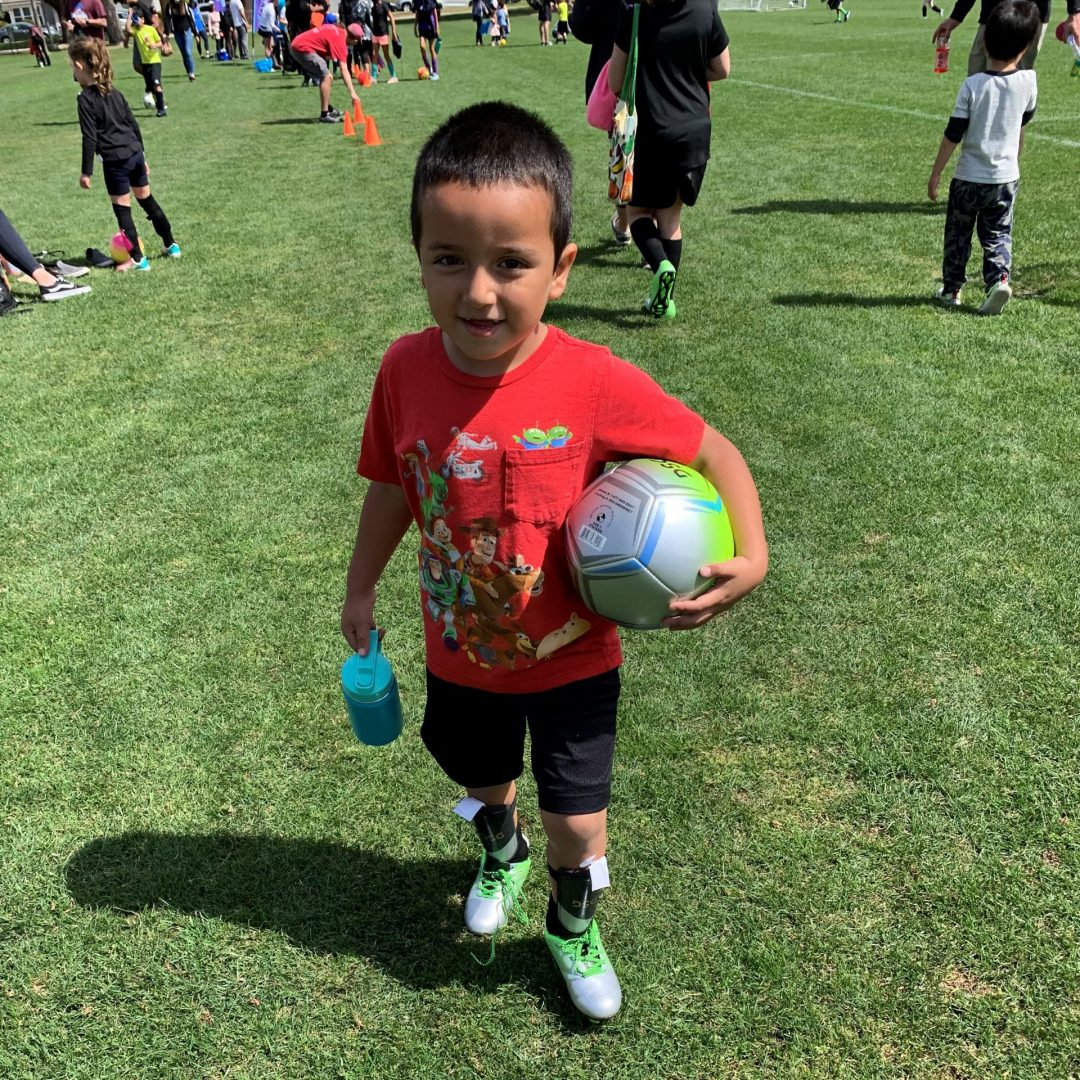 Male youth soccer player in California with ball, water bottle and in uniform on soccer field with All Kids Play financial assistance youth sports grant