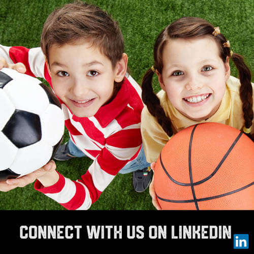 Youth sports boy soccer player and girl basketball player holding balls up and smiling