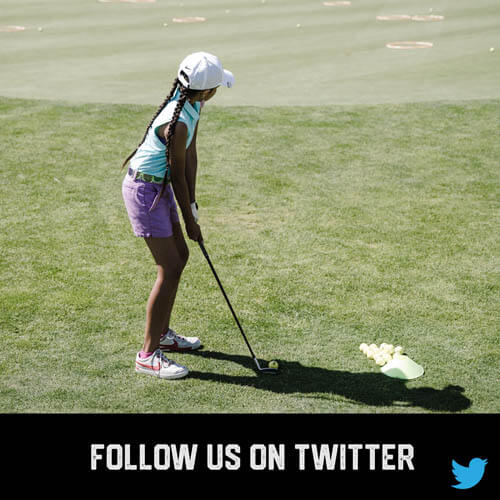 African American youth sport girl golfer teeing up to swing and hit a golf ball on a golf course