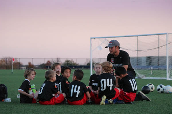 Youth sports boys soccer team sitting in a huddle with their coach teaching life lessons and sports skills on a soccer field