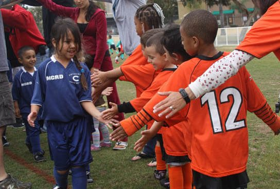 Coed multicultural diverse youth sports soccer teams shaking hands after a soccer match