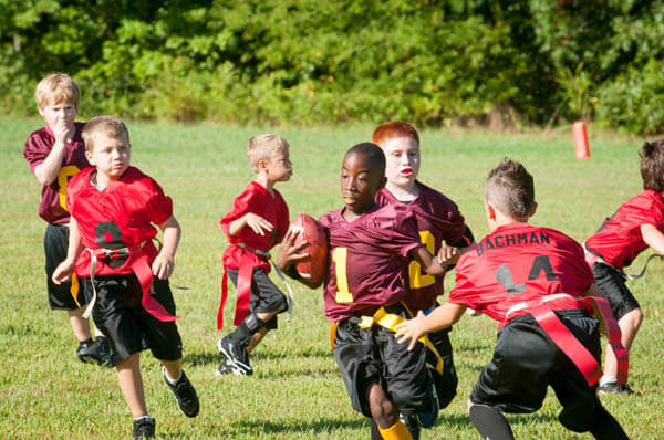 African American youth sports boy flag football player running against flag football team for a touchdown with a footbal on playing field