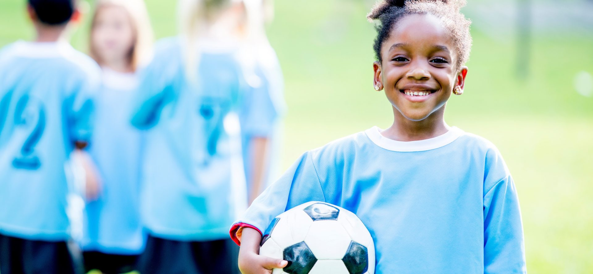 Youth female soccer athlete holding soccer ball on soccer field with team