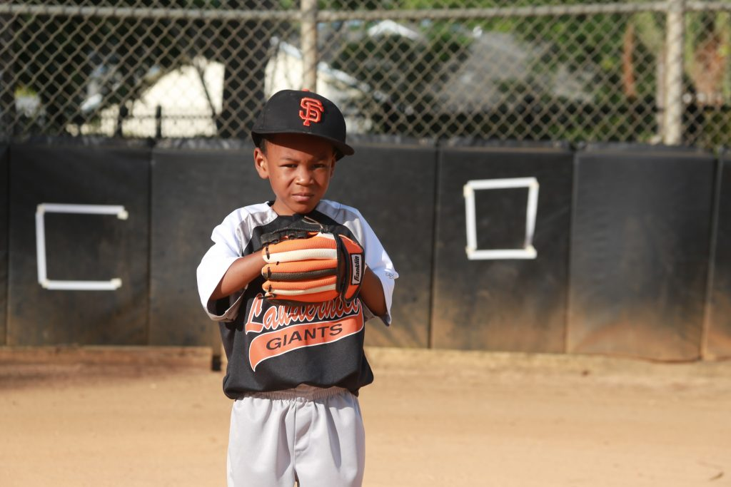 African American boy youth athlete on playing baseball with glove on baseball field