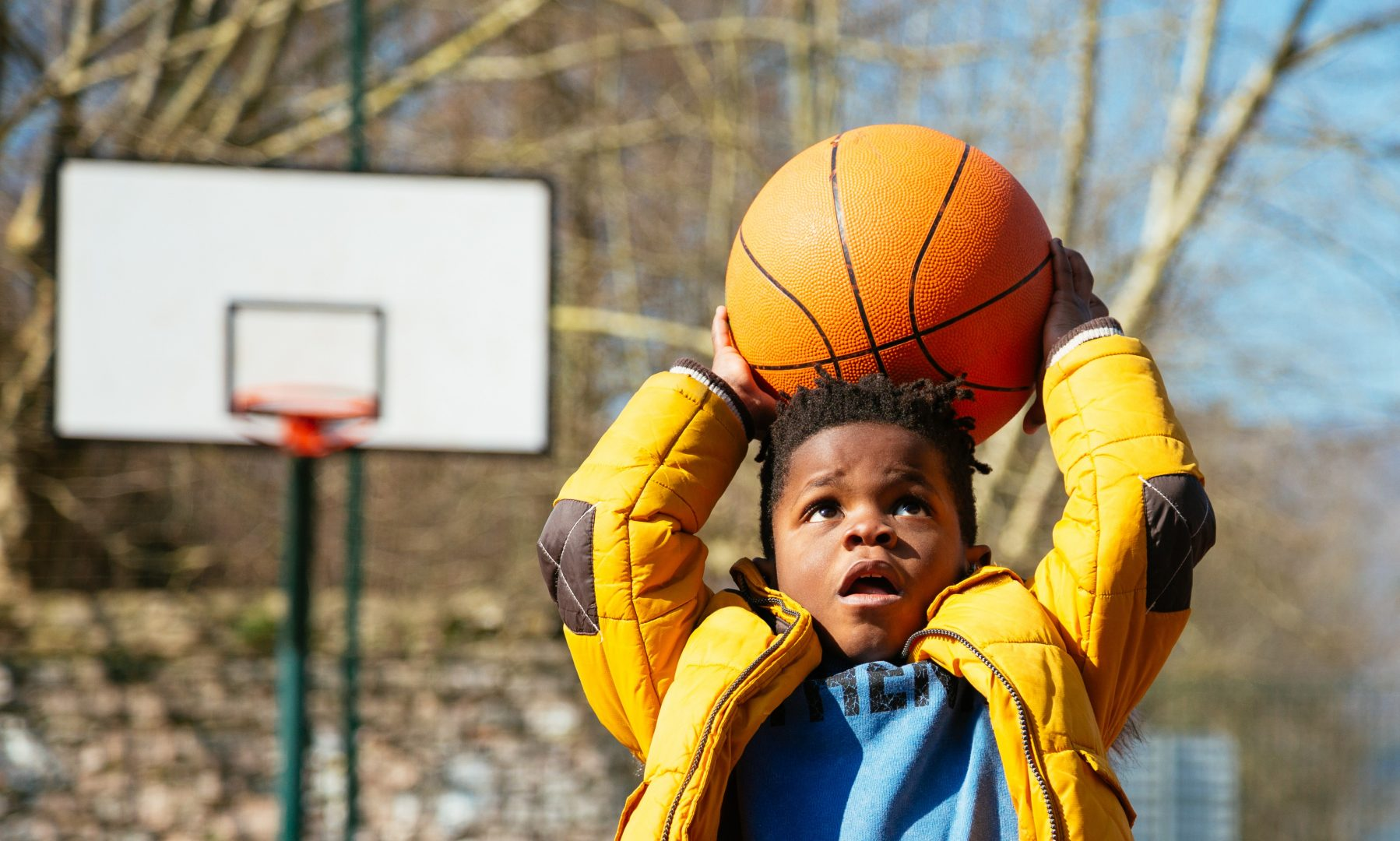African American little boy basketball player shooting a basketball at a playground