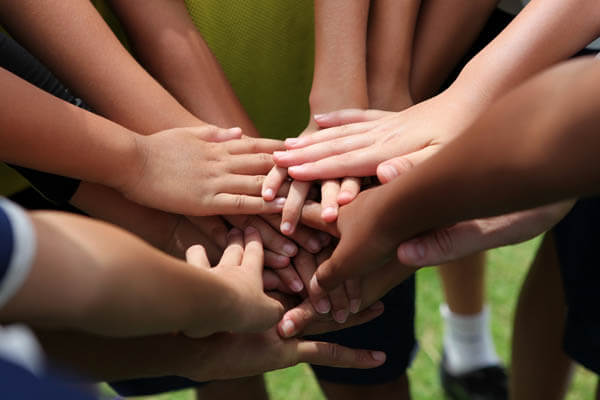 Multicultural diverse youth sports team huddle with hands in at a competition showing teamwork and dedication