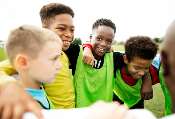 African American boy youth sports soccer players in a huddle happy to be part of a team
