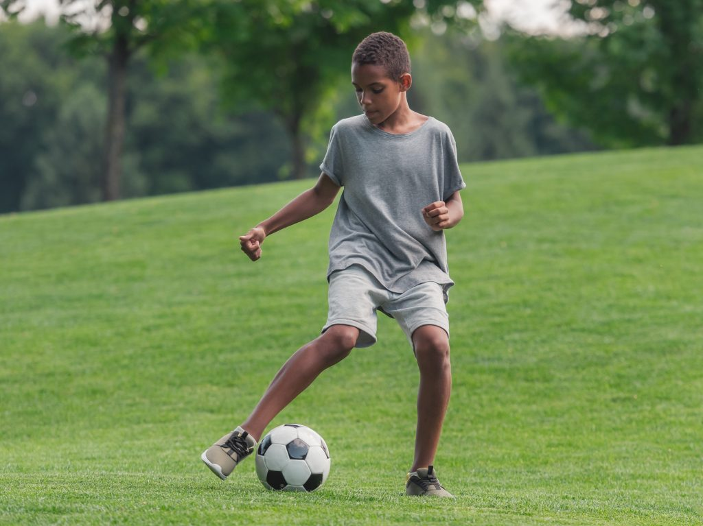 African American youth boy soccer playing dribbling the ball during practice alone