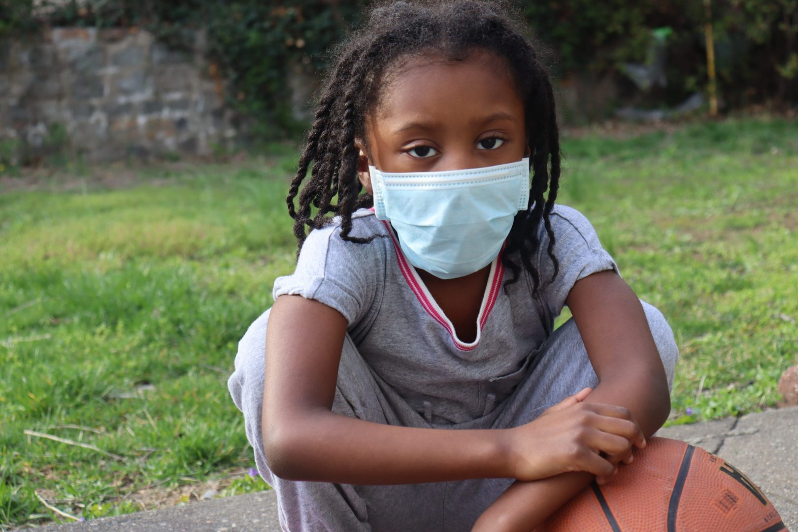 African American girl with mask during pandemic with a basketball