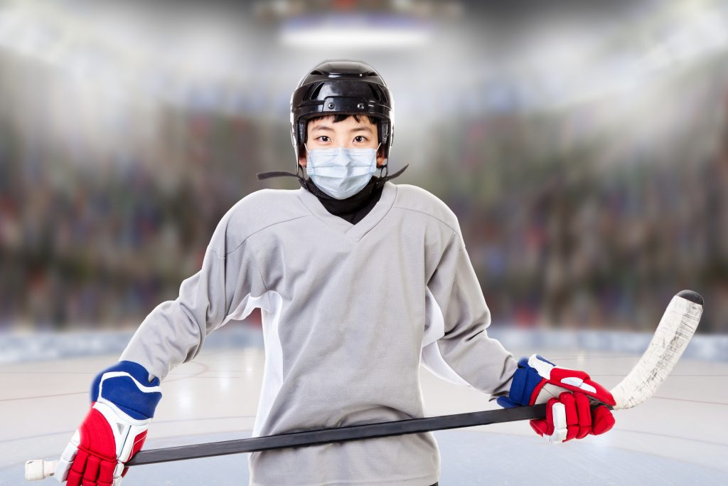 Asian youth male athlete hockey player with mask, stick and gear on hockey rink ice