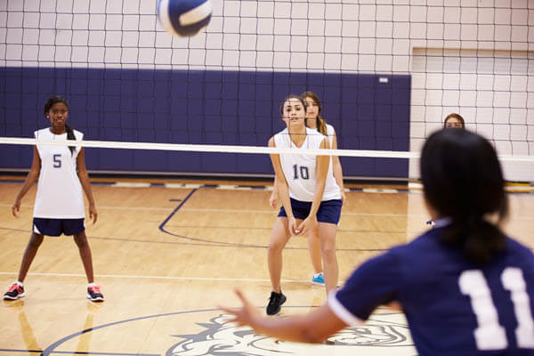African American and Caucasian youth sports girls volleyball players passing a volleyball over the net in a gym