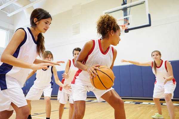 African American and Caucasian teenage girls youth sports basketball players practicing basketball in a scrimmage on a basketball court