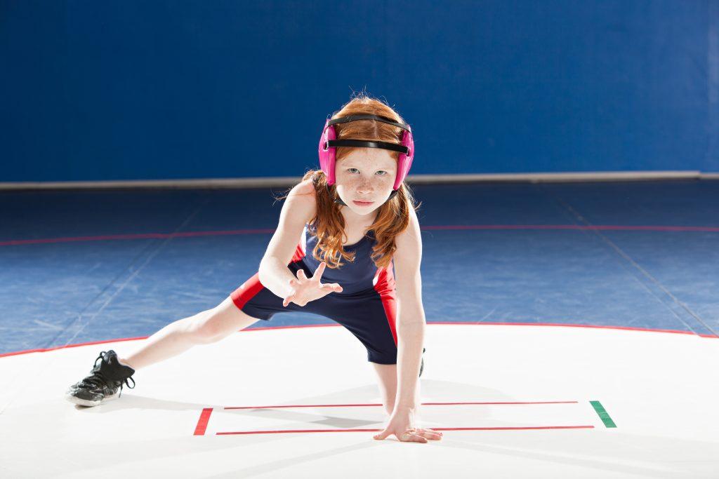 Girl youth sports wrestler on wrestling mat warming up