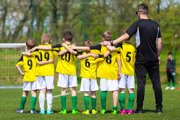 Boys youth sports soccer team and coach standing in partnership and teamwork on a soccer field