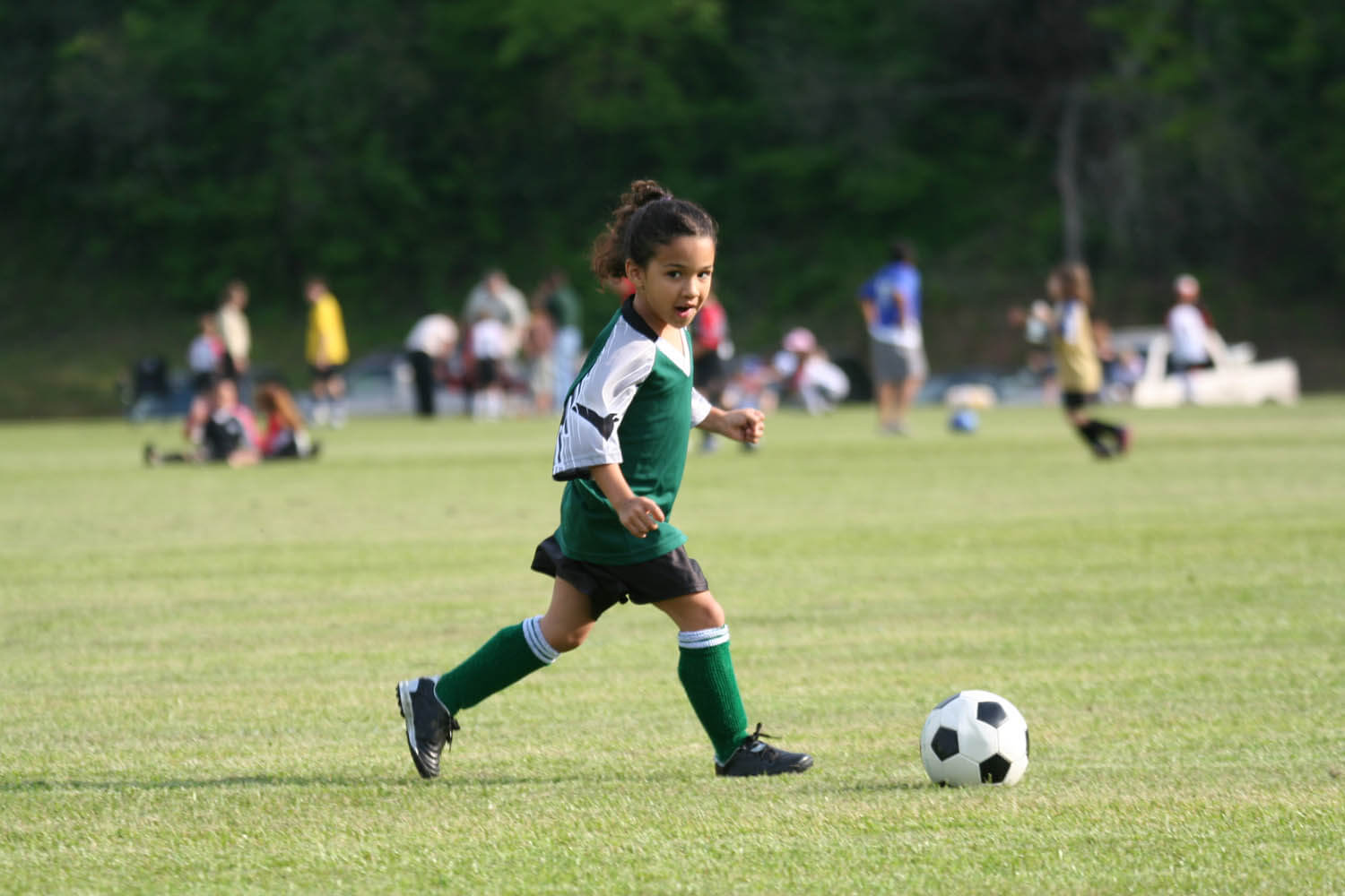 African American girl soccer player kicking a ball in a youth sports soccer match