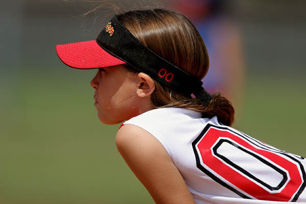 Youth sports girl softball player ready to field a softball during a game.