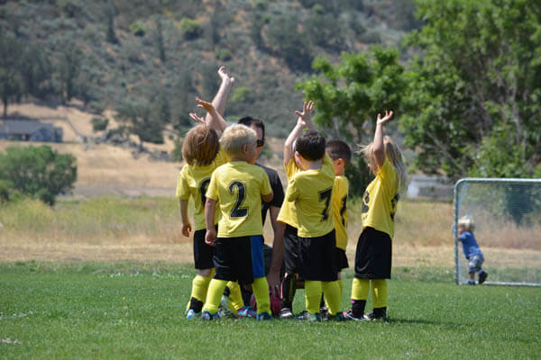 Coed youth sports soccer team in a huddle with coach hands raised asking questions on a soccer field