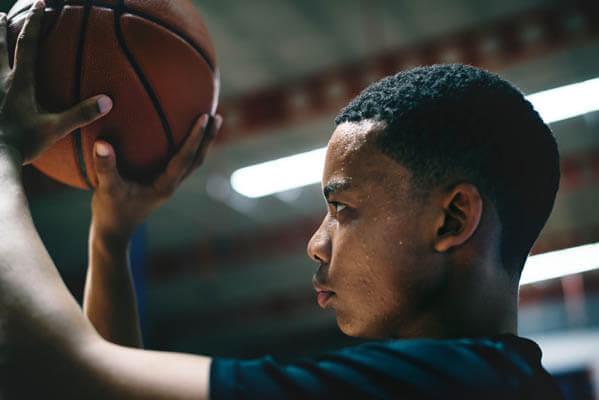 African American youth sports teen boy basketball player shooting a basketball on a basketball court